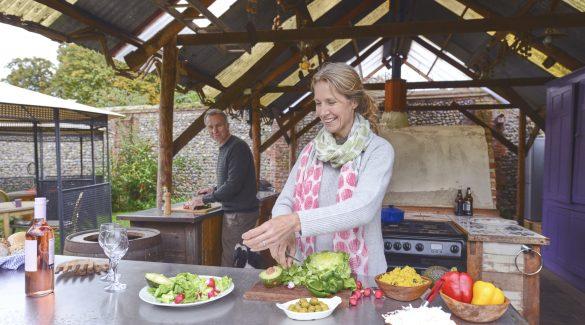 Couple marié qui prépare à manger dans sa cuisine extérieure