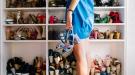 femme debout tenant des chaussures à la main devant un placard rempli de chaussures