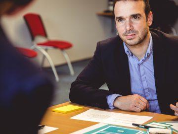 homme assis devant une table avec un coude posé sur la table portant une chemise bleue et une veste de costume sombre