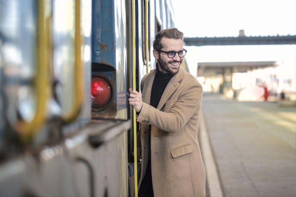 homme portant des lunettes un manteau beige long et un pull noir à col roulé