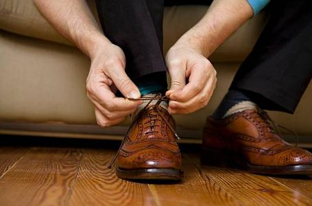 homme qui lace ses chaussures marron