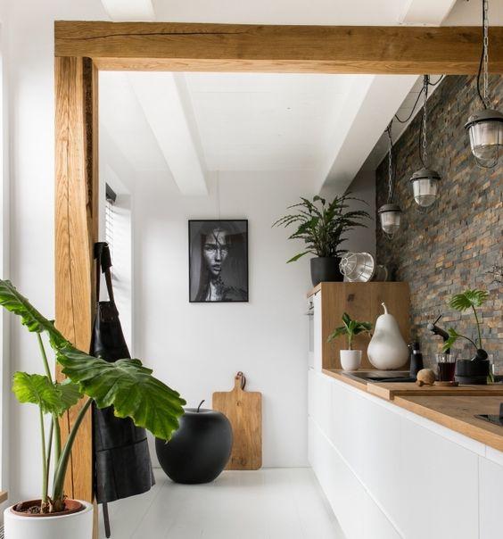 cuisine semi fermée de couleur blanc et bois avec mur en pierre et plantes vertes