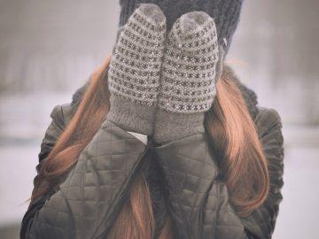 femme aux cheveux longs portant un bonnet foncé une veste kaki et des moufles se cachant le visage