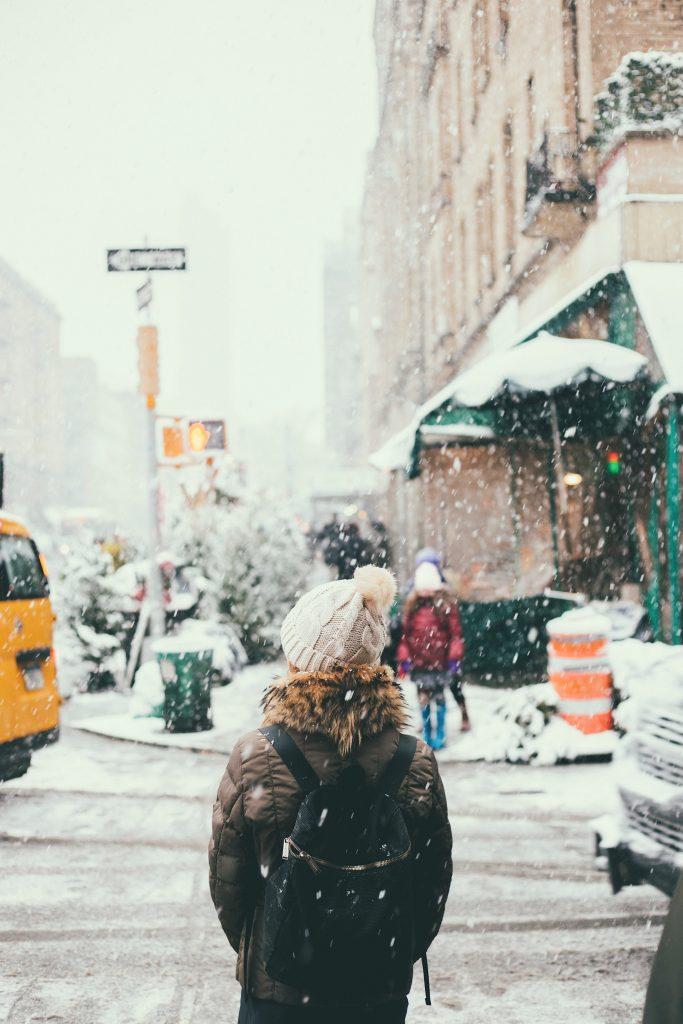 femme dans la rue sous la neige portant un bonnet clair une doudoune et un sac à dos noir