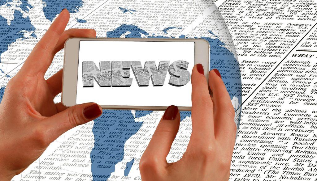 """Deux mains tenant un smartphone sur lequel est écrit """"news"""""""