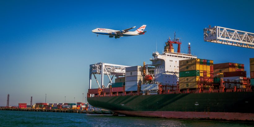 bateau avec conteneurs et avion qui passe au-dessus