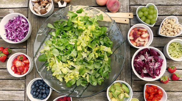 saladier de salade verte avec ingrédients pour salade composée dans des petits bols autour