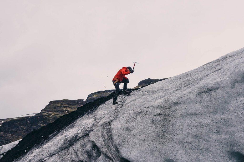 personne faisant de l'alpinisme sur la glace avec un piolet