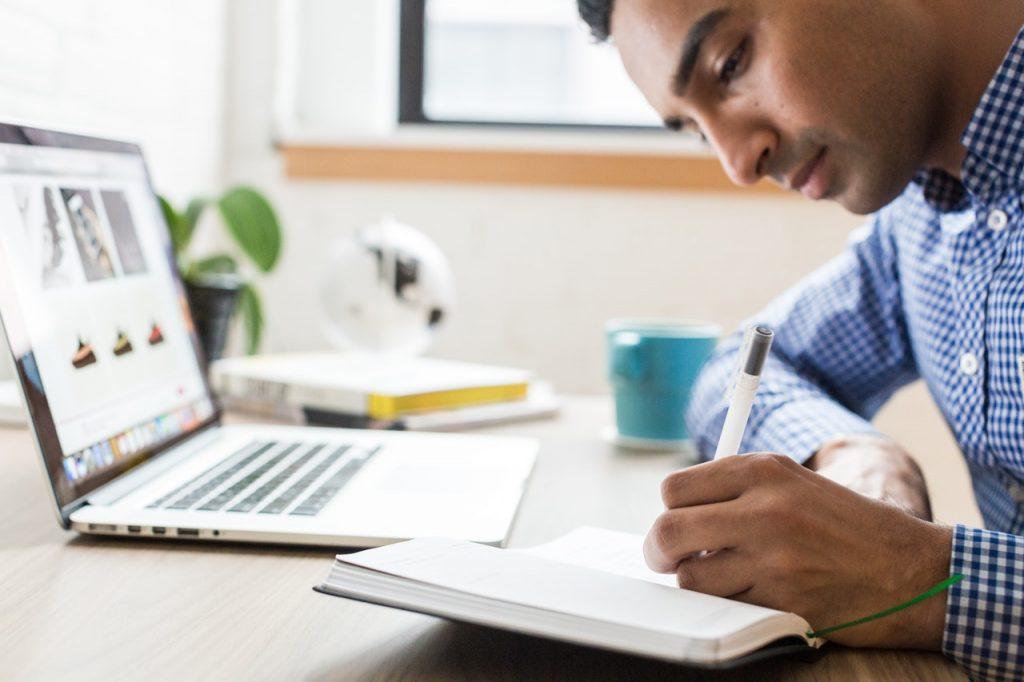 homme qui prend des notes devant un ordinateur portable