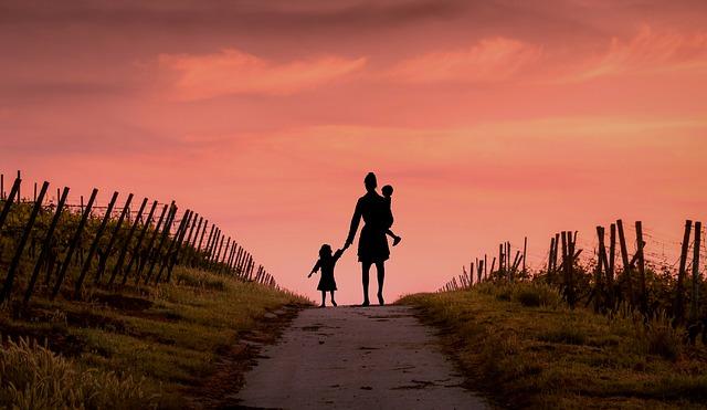 femme et enfant au bout d'un chemin avec couchée de soleil