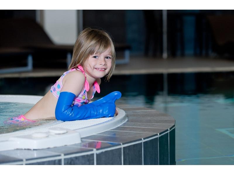 enfant avec un protège plâtre dans une piscine